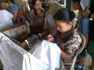 A Balinese woman making batik with traditional tools