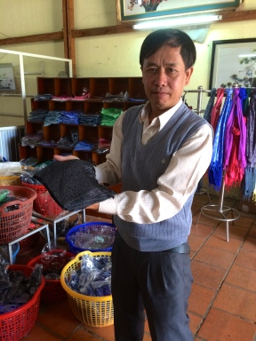 Mr. Chien holding cloth made from one cocoon.