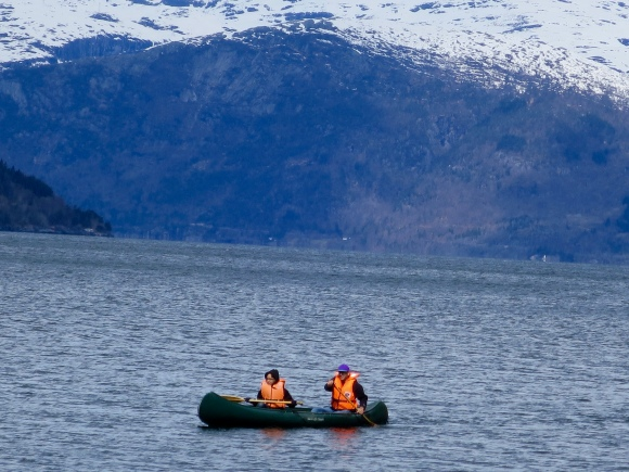 Out in the fjord with one kid caring for another kid's hat